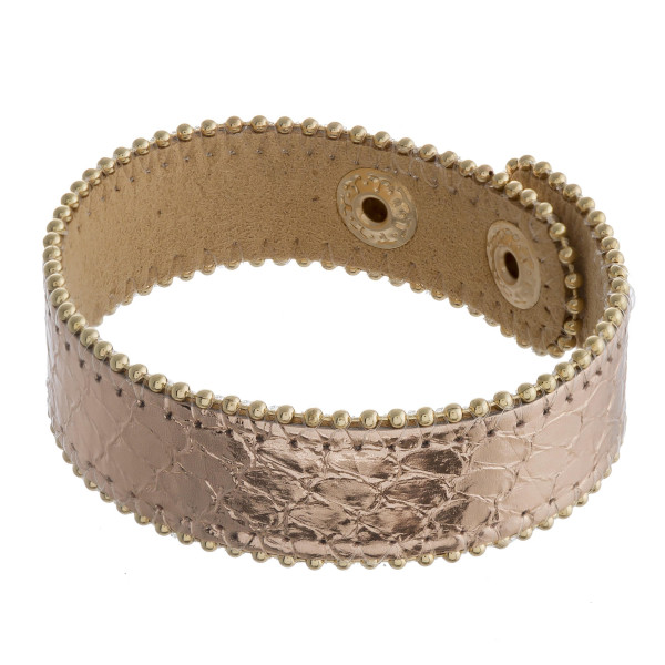 """Genuine leather bracelet featuring metallic snakeskin details and a snap closure. Approximately 3"""" in diameter. Fits up to a 6"""" wrist."""