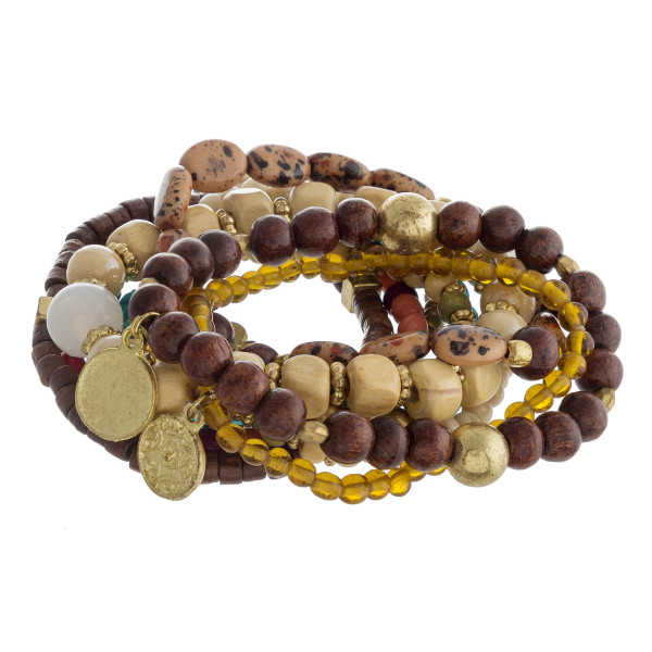 """Bracelet set featuring eight beaded stretch bracelets with wood and natural stone bead details and gold metal accents. Approximately 3"""" in diameter unstretched. Fits up to a 6"""" wrist."""