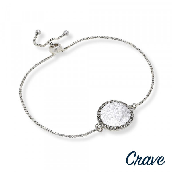 "Dainty bolo bracelet featuring a metal circular focal with cubic zirconia accents and  adjustable closure. Approximately 3"" in diameter. Fits up to a 6"" wrist."