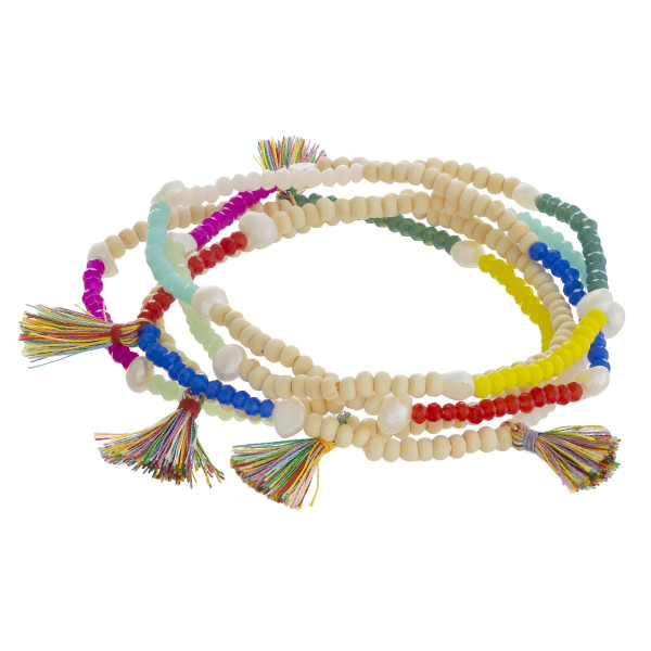 "Beaded stretch bracelet set featuring faceted and wood bead details with tassel and pearl accents. Approximately 3"" in diameter unstretched. Fits up to a 6"" wrist."