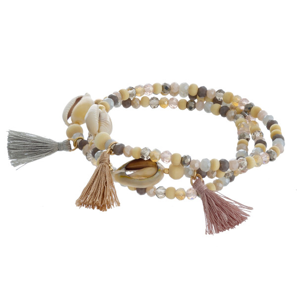 "Trio beaded stretch bracelet set featuring faceted bead details with tassel and puka shell accents. Approximately 3"" in diameter unstretched. Fits up to a 6"" wrist."