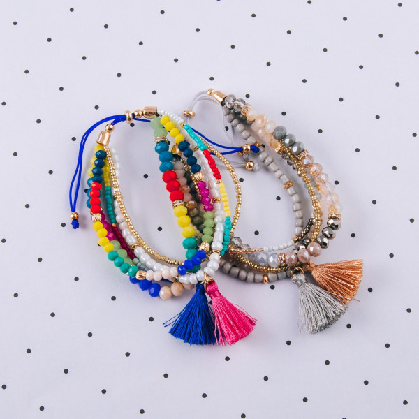 """Multi strand bolo style bracelet featuring faceted bead details with gold accents and tassel charms. Approximately 3"""" in diameter. Fits up to a 6"""" wrist."""