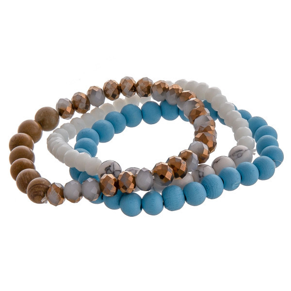 """Trio stretch bracelet set featuring natural stone, iridescent, and wood inspired bead details. Approximately 3"""" in diameter unstretched. Fits up to 6"""" wrist."""