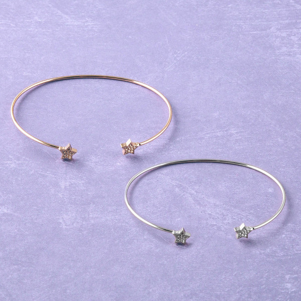 """Dainty metal cuff bracelet featuring star accents with cubic zirconia details. Approximately 3"""" in diameter. Fits up to a 6"""" wrist."""