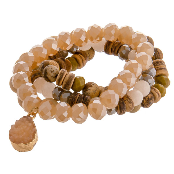 """Natural stone beaded stretch bracelet set featuring a druzy teardrop charm with wood and faceted bead details. Approximately 3"""" in diameter unstretched. Fits up to a 6"""" wrist."""