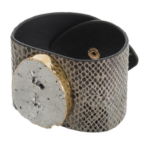"Faux leather snakeskin bracelet featuring a druzy focal with an adjustable button snap closure. Approximately 3"" in diameter and 2"" wide."