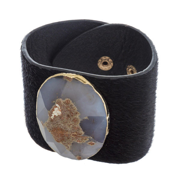 "Fur faux leather bracelet featuring a semi precious stone focal with an adjustable snap button closure. Approximately 3"" in diameter and 2"" in width."