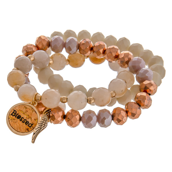 """Natural faceted acrylic beaded stretch bracelet set featuring a cork """"Blessed"""" charm with a gold angel wing and pearl accent. Approximately 3"""" in diameter unstretched. Fits up to a 6"""" wrist."""