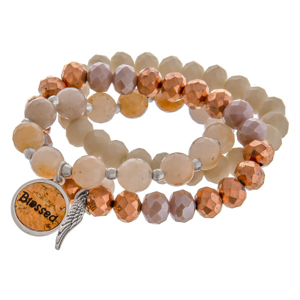 """Natural faceted acrylic beaded stretch bracelet set featuring a cork """"Blessed"""" charm with a silver angel wing and pearl accent. Approximately 3"""" in diameter unstretched. Fits up to a 6"""" wrist."""