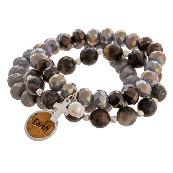 """Smokey Grey faceted acrylic beaded stretch bracelet set featuring a cork """"Faith"""" charm with a silver cross and pearl accent. Approximately 3"""" in diameter unstretched. Fits up to a 6"""" wrist."""
