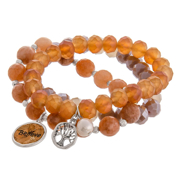 """Smokey Brown faceted acrylic beaded stretch bracelet set featuring a cork """"Believe"""" charm with a silver tree of life charm and pearl accent. Approximately 3"""" in diameter unstretched. Fits up to a 6"""" wrist."""