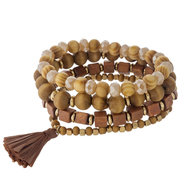 "Wood beaded stretch bracelet set featuring faceted bead details with a raffia tassel accent. Approximately 3"" in diameter unstretched. Fits up to a 6"" wrist."