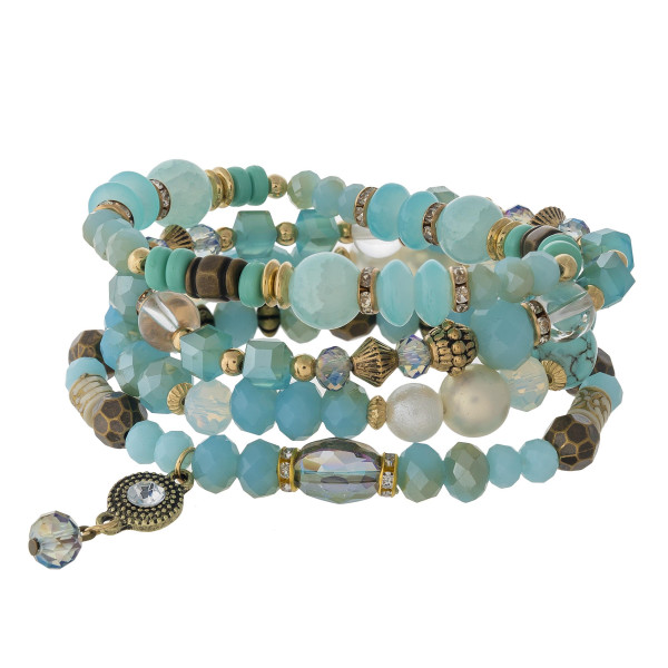 """Aqua beaded stretch bracelet featuring natural stone, wood, and faceted bead details with a tiny charm. Approximately 3"""" in diameter unstretched. Fits up to a 6"""" wrist."""