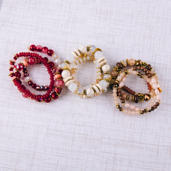 """Beige beaded bracelet set featuring natural stone, iridescent, faceted and plastic bead details with gold bead accents and a """"Love"""" charm. Approximately 3"""" in diameter unstretched. Fits up to a 6"""" wrist."""
