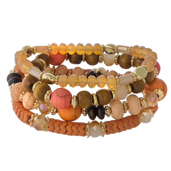 "Peach beaded stretch bracelet set featuring natural stone, iridescent, wood and faceted bead details with gold bead accents. Approximately 3"" in diameter unstretched. Fits up to a 6"" wrist."
