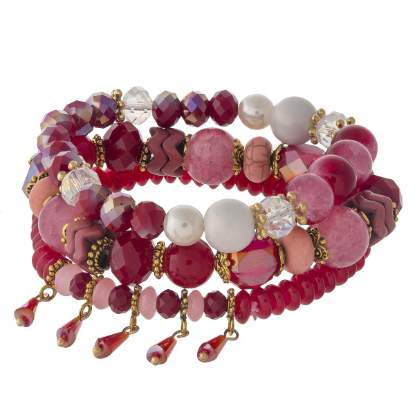 """Red beaded stretch bracelet set featuring natural stone, iridescent and faceted bead details with gold flower accents and bead tassels. Approximately 3"""" in diameter unstretched. Fits up to a 6"""" wrist."""