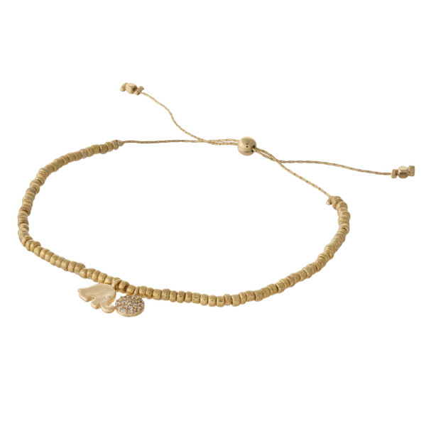 """Dainty seed beaded bolo bracelet featuring an elephant and disc charm with cubic zirconia details. Approximately 3"""" in diameter. Fits up to 6"""" wrist."""