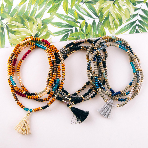 """Wood, iridescent and faceted beaded stretch wrap bracelet featuring gold accents and a tassel detail. Approximately 3"""" in diameter unstretched. Fits up to a 6"""" wrist."""