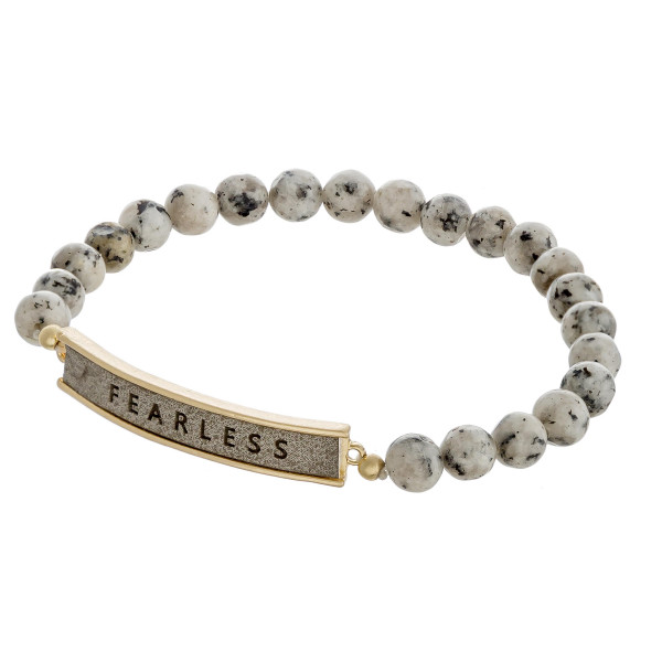 """Natural stone beaded stretch bracelet featuring a faux leather focal with """"Fearless"""" engraved details. Approximately 3"""" in diameter unstretched. Fits up to a 6"""" wrist."""