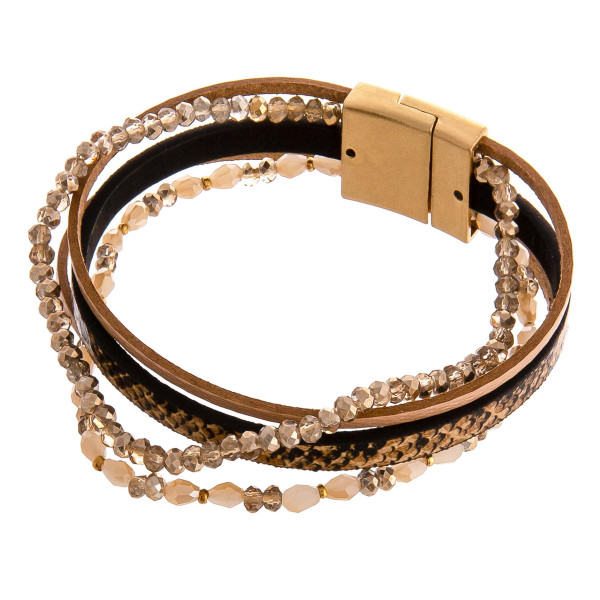 """Multi strand faux leather bracelet featuring snakeskin print and iridescent beaded details with a magnetic closure. Approximately 3"""" in diameter. Fits up to a 6"""" wrist."""