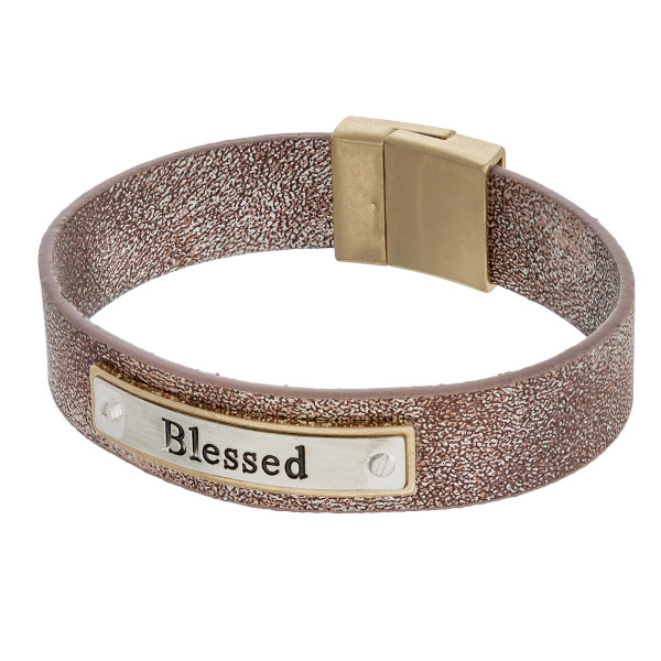"""Metallic faux leather bracelet featuring a metal focal with """"Blessed"""" engraved details and a magnetic closure. Approximately 3"""" in diameter. Fits up to a 6"""" wrist."""