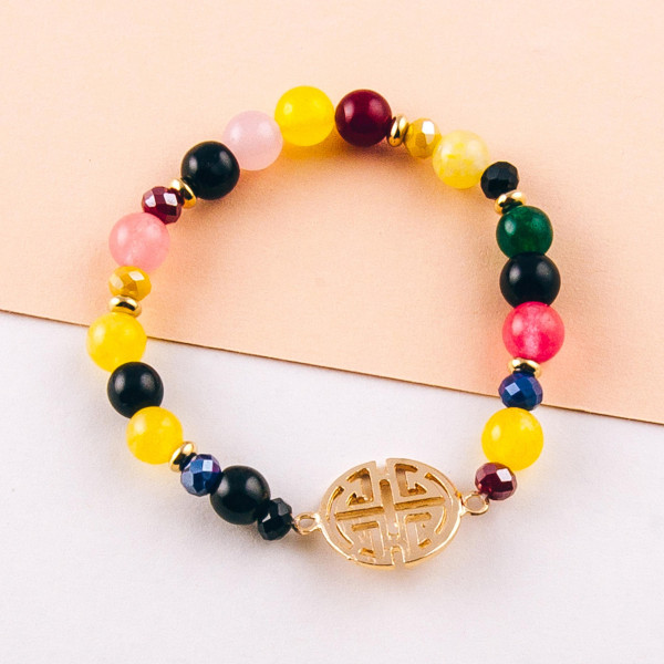 """Natural stone inspired beaded stretch bracelet featuring a gold metal focal. Approximately 3"""" in diameter unstretched. Fits up to a 6"""" wrist."""