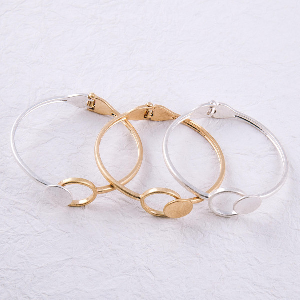 """Hinged bangle bracelet featuring a circular focal. Approximately 3"""" in diameter."""