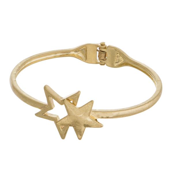 "Gold hinged bangle bracelet featuring a star focal. Approximately 3"" in diameter. Fits up to a 6"" wrist."