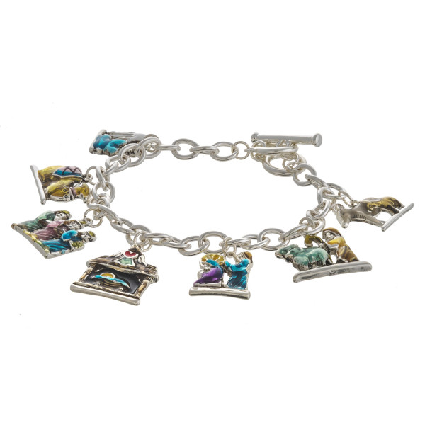 """Enamel coated Jesus assorted Christmas charm bracelet with toggle clasp closure. Approximately 3"""" in diameter. Fits up to a 6"""" wrist."""