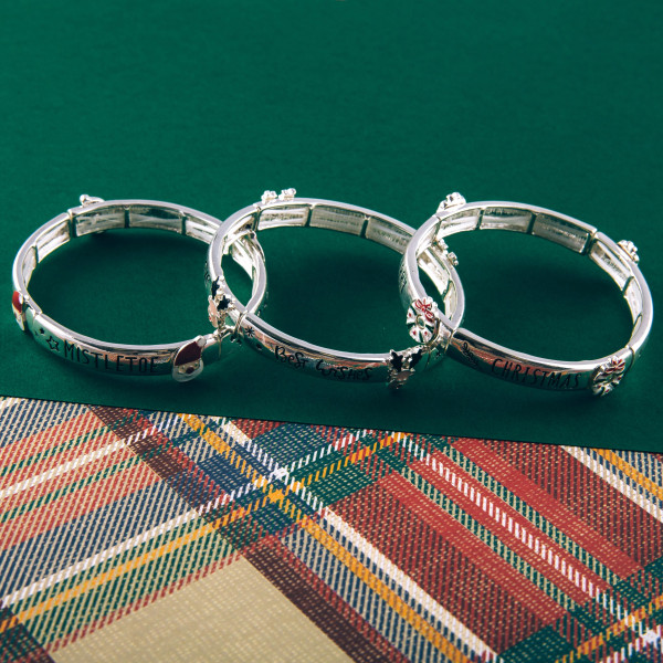 """""""Meet me under the Mistletoe"""" engraved stretch bracelet featuring an enamel coated accent. Approximately 2.5"""" in diameter unstretched. Fits up to a 5"""" wrist."""
