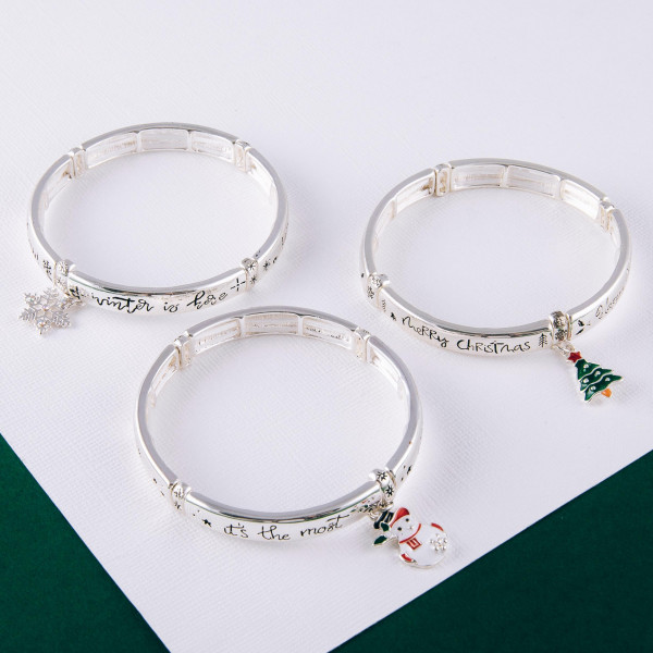 """""""Happy Holiday's"""" engraved stretch bracelet with enamel coated charm. Approximately 2.5"""" in diameter unstretched. Fits up to a 5"""" wrist."""