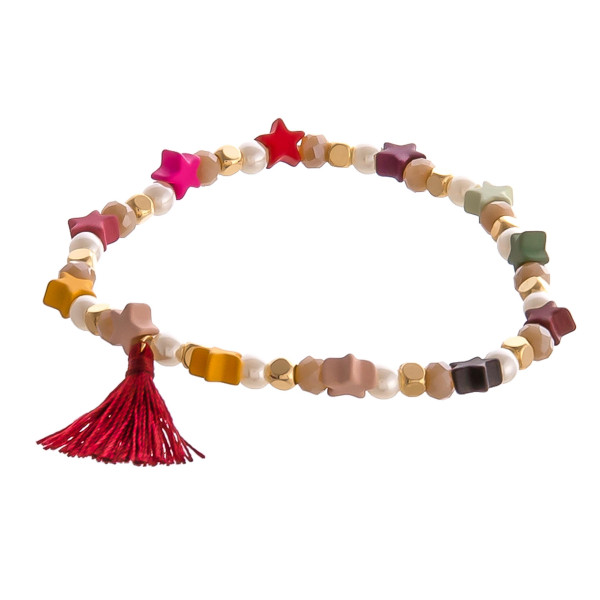 """Color block star and pearl beaded stretch bracelet with tassel accent. Approximately 3"""" in diameter unstretched. Fits up to a 6"""" wrist."""