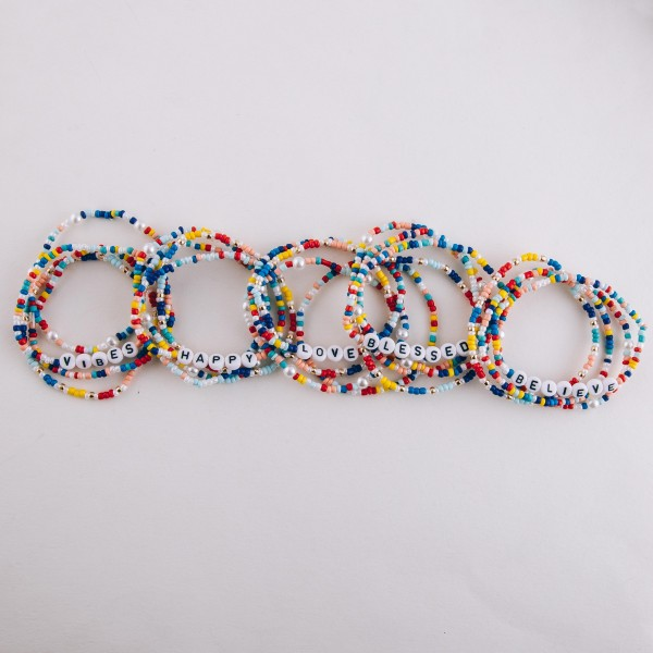 """Multicolor seed beaded """"Believe"""" letter stretch bracelet set with pearl details.  - 4pcs/pack - Approximately 3"""" in diameter unstretched - Fits up to a 7"""" wrist"""