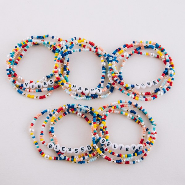 """Multicolor seed beaded """"Blessed"""" letter stretch bracelet set with pearl details.  - 4pcs/pack - Approximately 3"""" in diameter unstretched - Fits up to a 7"""" wrist"""