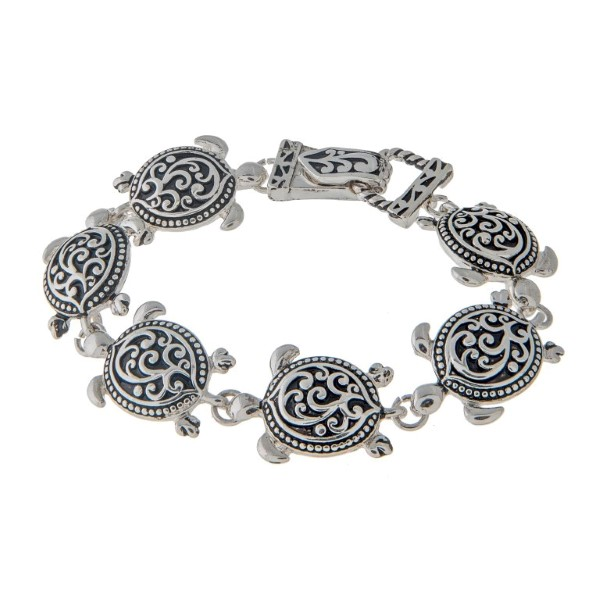 "7 1/2"" around silver tone charm bracelet featuring swimming sea turtles in a filigree design."