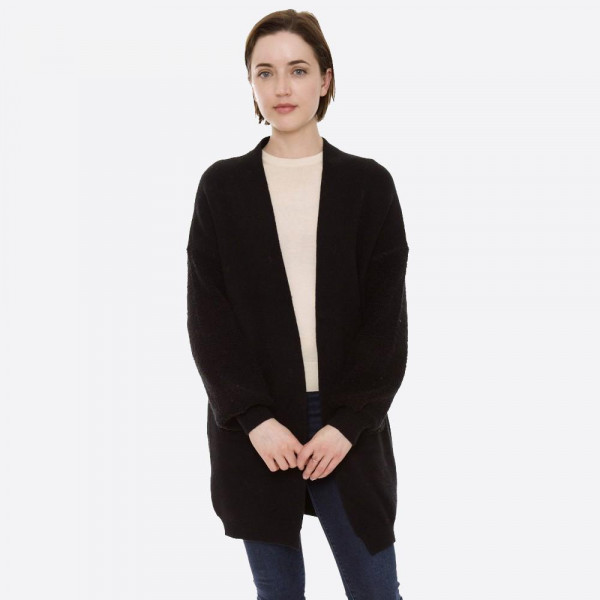 "Solid color knit cardigan with terry cloth balloon sleeves and front pocket details.  - One size fits most 0-14 - Approximately 32"" in length - 100% Polyester"