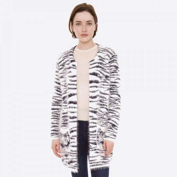 "Fuzzy zebra print cardigan with front pocket details.  - One size fits most 0-14 - Approximately 30"" in length - 100% Polyester"