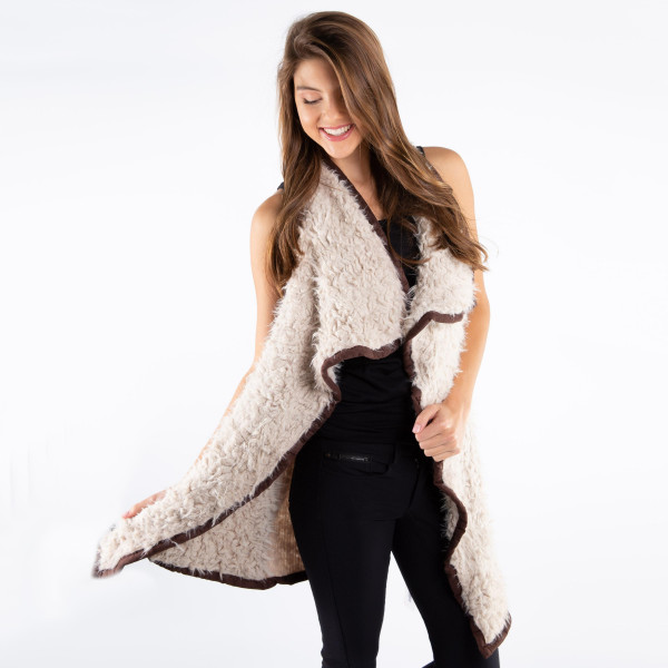 Ivory and dark brown faux fur vest with faux front pockets and a tapered front. 100% polyester. One size fits most.