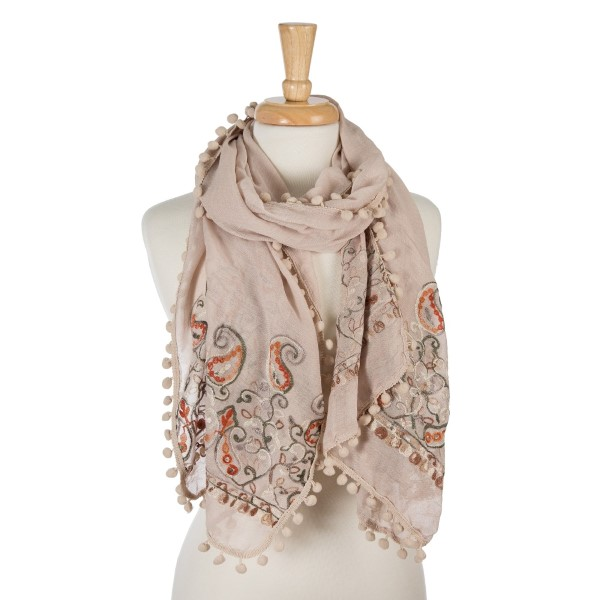 "Beige, lightweight scarf with floral embroidery and pom poms on the outer trim. 65% polyester and 35% viscose. Measures 26"" x 70"" in size."