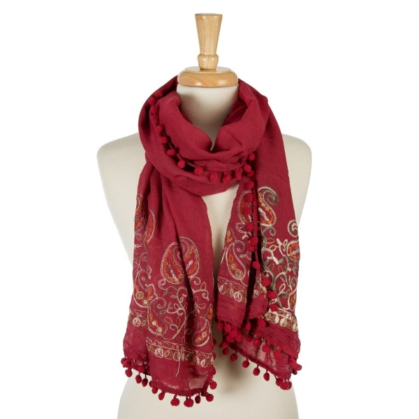 "Burgundy, lightweight scarf with floral embroidery and pom poms on the outer trim. 65% polyester and 35% viscose. Measures 26"" x 70"" in size."