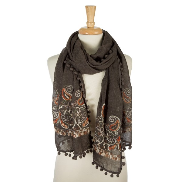 "Charcoal gray, lightweight scarf with floral embroidery and pom poms on the outer trim. 65% polyester and 35% viscose. Measures 26"" x 70"" in size."