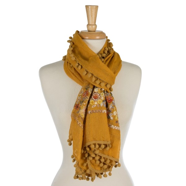 """Lightweight, open scarf with an embroidered, floral print and a pom pom trim. 65% polyester and 35% viscose. Measures 76"""" x 28"""" in size."""