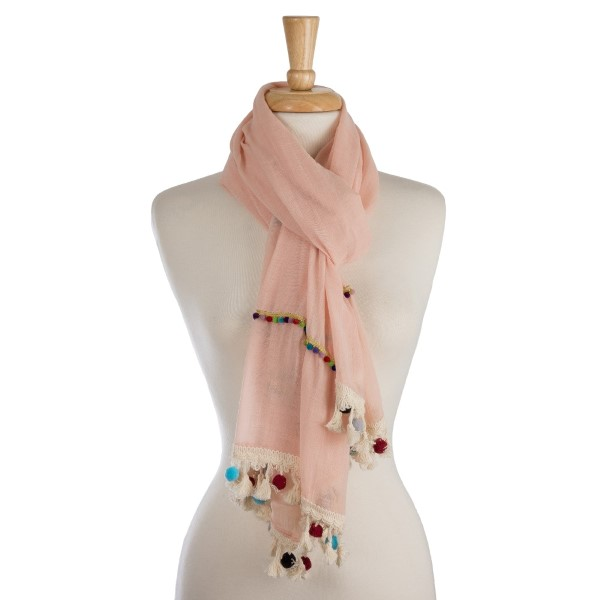 "Lightweight, solid scarf with colorful pom pom trim along the edge. 100% polyester. Measures 27"" x 72"" in size."