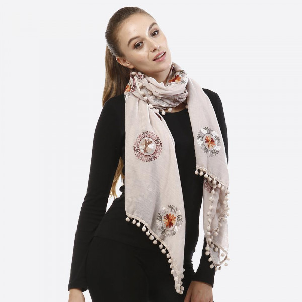Lightweight embroidered scarf with pom pom detail. 100% acrylic.