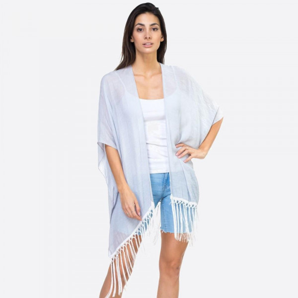 "Solid blue kimono with lace down the back and fringe detailing. One size fits most 0-14. Measures approximately 37"" x 27"" in size. 65% Polyester, 35% Cotton."