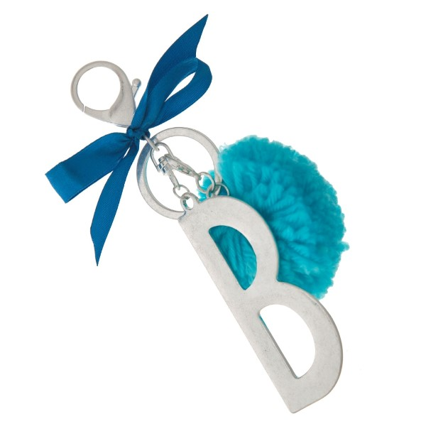 "Silver tone key chain or bag charm with a block 'B' initial pendant and blue pom pom. Approximately 5.5"" in length."