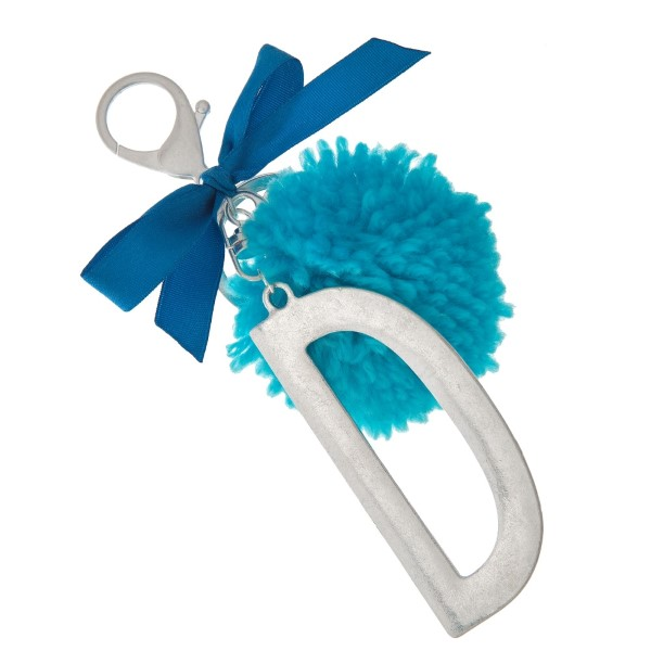 "Silver tone key chain or bag charm with a block 'D' initial pendant and blue pom pom. Approximately 5.5"" in length."
