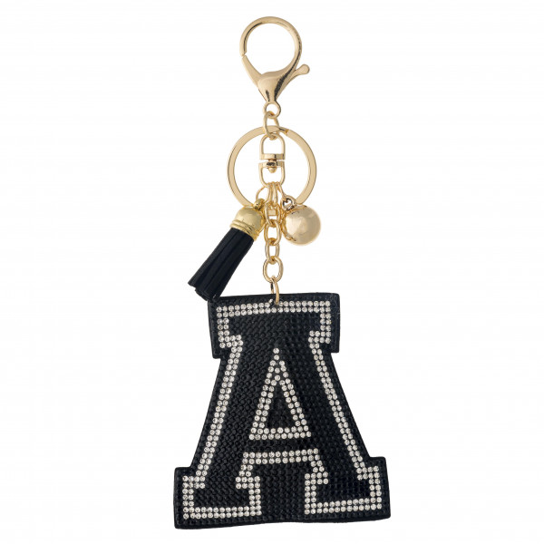 "Black initial pillow keychain/bag charm featuring rhinestone details and a tassel accent. Initial approximately 2.5"". Approximately 6"" in length overall."