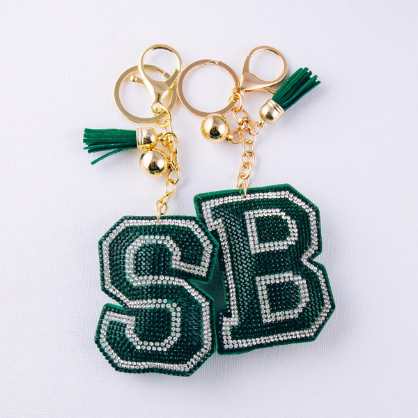 "Green initial pillow keychain/bag charm featuring rhinestone details and a tassel accent. Initial approximately 2.5"". Approximately 6"" in length overall."