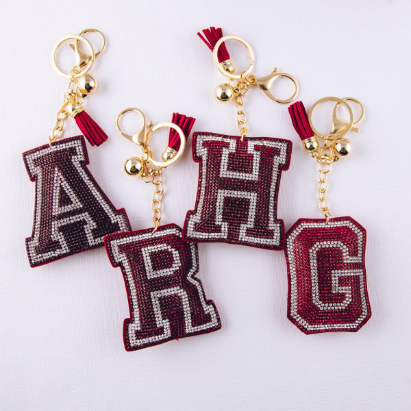 "Red initial pillow keychain/bag charm featuring rhinestone details and a tassel accent. Initial approximately 2.5"". Approximately 6"" in length overall."